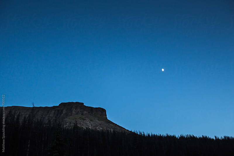 Moon in blue evening sky over mountains by Matthew Spaulding for Stocksy United