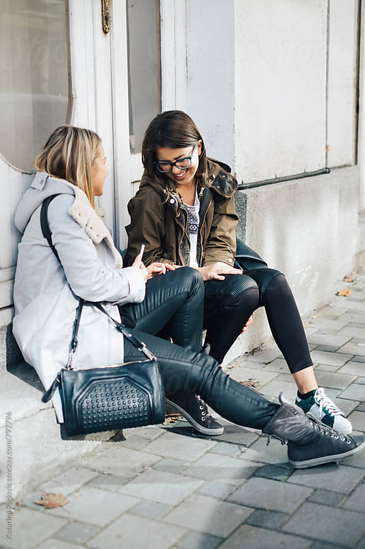 Two Female Friends Sitting on a Steps and Chatting  by Katarina Radovic for Stocksy United