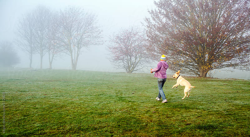 Woman walking her dog in autumn mist by kkgas for Stocksy United