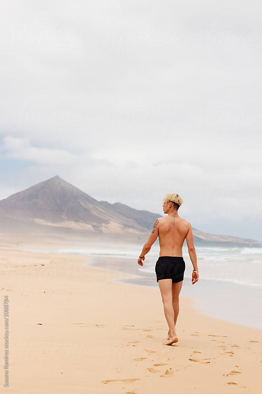 Blond man walking along a beach with mountains by Susana Ramírez for Stocksy United