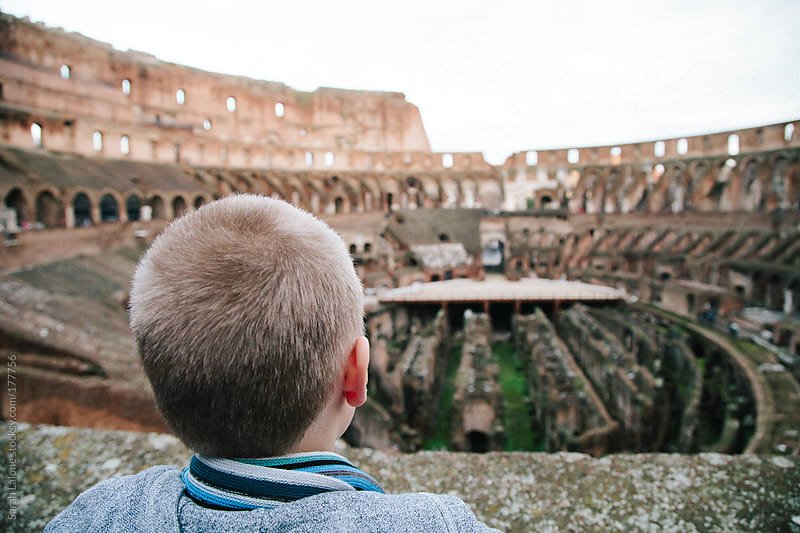a little guy looking out over the inside of the colosseum by Sarah Lalone for Stocksy United