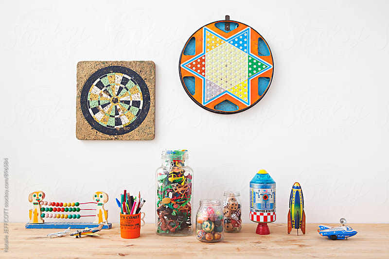 Collection of old toys and games on a table by Natalie JEFFCOTT for Stocksy United