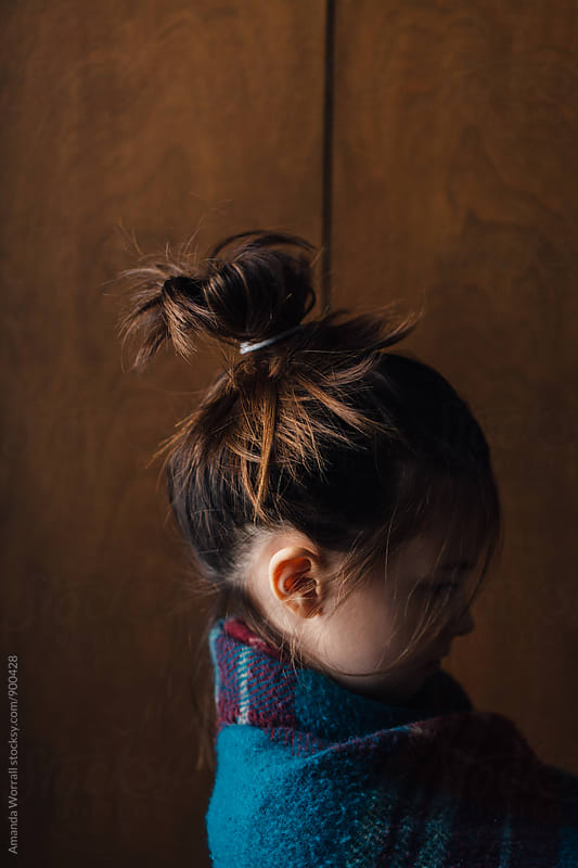 Profile portrait of young girl wrapped in a blanket, hair up in a messy bun by Amanda Worrall for Stocksy United