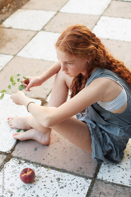 Red hair young girl sitting on the ground in a relaxed moment by Miquel Llonch for Stocksy United