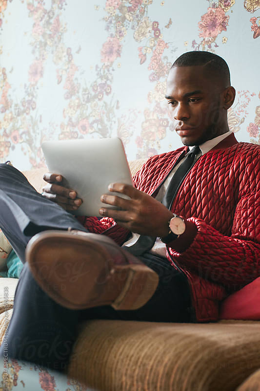 Stylish Young Black Man Sitting on Sofa and Reading on Digital Tablet by Julien L. Balmer for Stocksy United