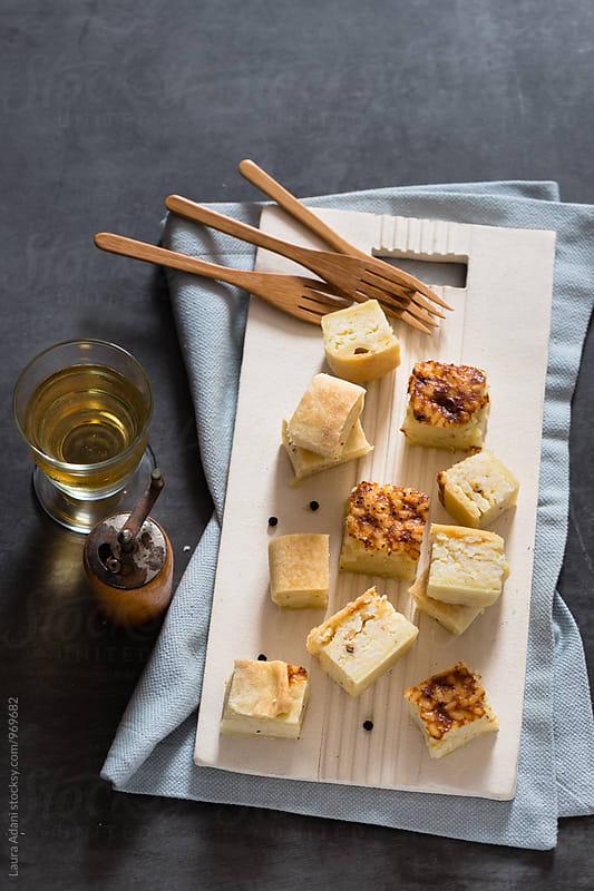 Rice italian savory tart in portions on a cut board by Laura Adani for Stocksy United