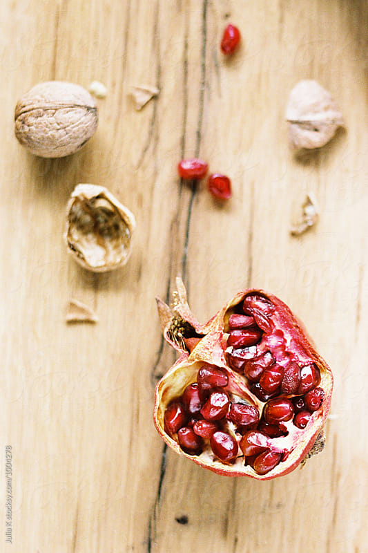 Garnet and walnuts on a table by Julia Kaptelova for Stocksy United