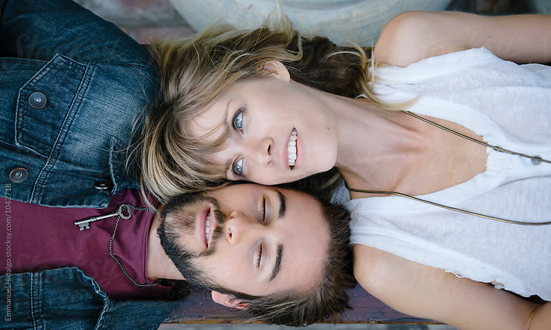 Couple lying down on a bench by Emmanuel Hidalgo for Stocksy United