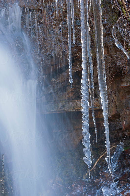 Icicles formed from the frozen spray of a waterfall by David Smart for Stocksy United