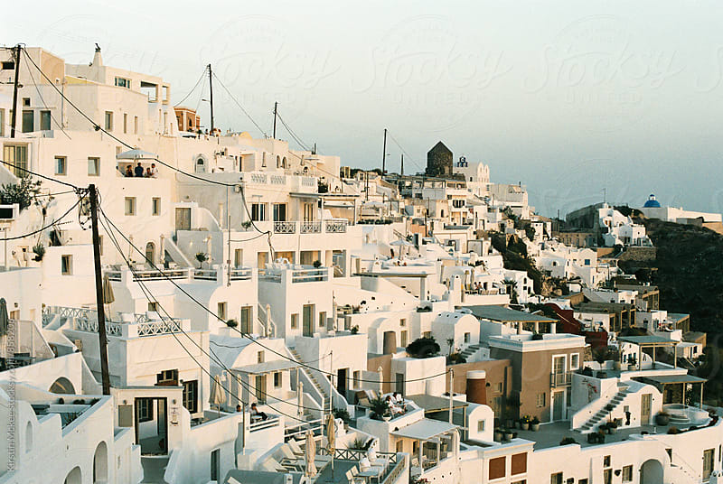 Sunset over buildings in Fira, Santorini by Kirstin Mckee for Stocksy United