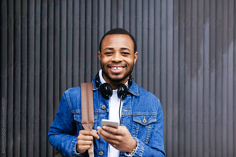Portrait of an african american man holding his phone outside. by BONNINSTUDIO for Stocksy United