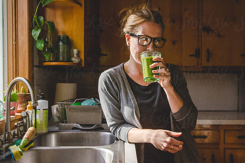 Woman standing beside kitchen sink with green smoothie by Lindsay Crandall for Stocksy United