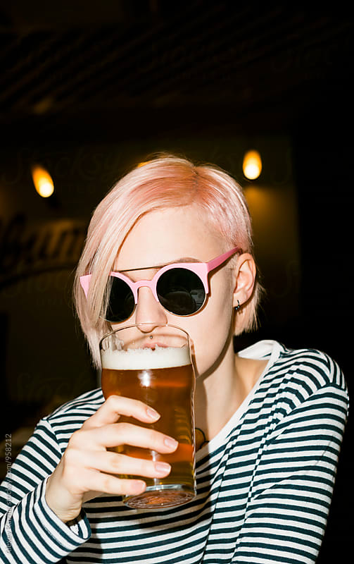 cool young woman with pink hair drinking a beer. by Vesna for Stocksy United