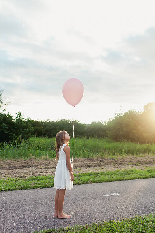 Barefoot little girl on a road looking up at her pink balloon by Cindy Prins for Stocksy United