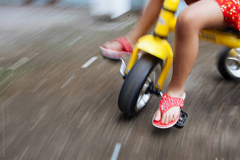 Little girl riding a tricycle,motion blur by Saptak Ganguly for Stocksy United