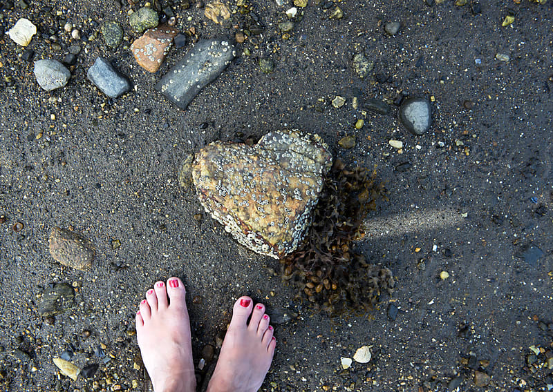 Woman's feet stand next to a heart shaped rock covered in barnacles and seaweed by Cara Slifka for Stocksy United
