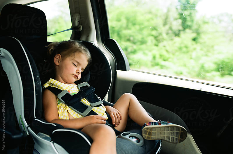 little girl sleeping in carseat by Maria Manco for Stocksy United