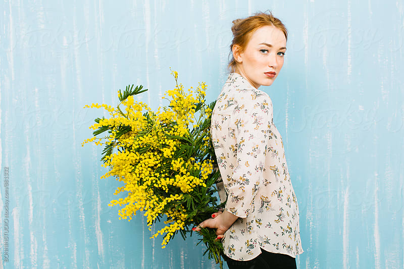 Young ginger woman holding a bouquet of yellow flowers. by BONNINSTUDIO for Stocksy United