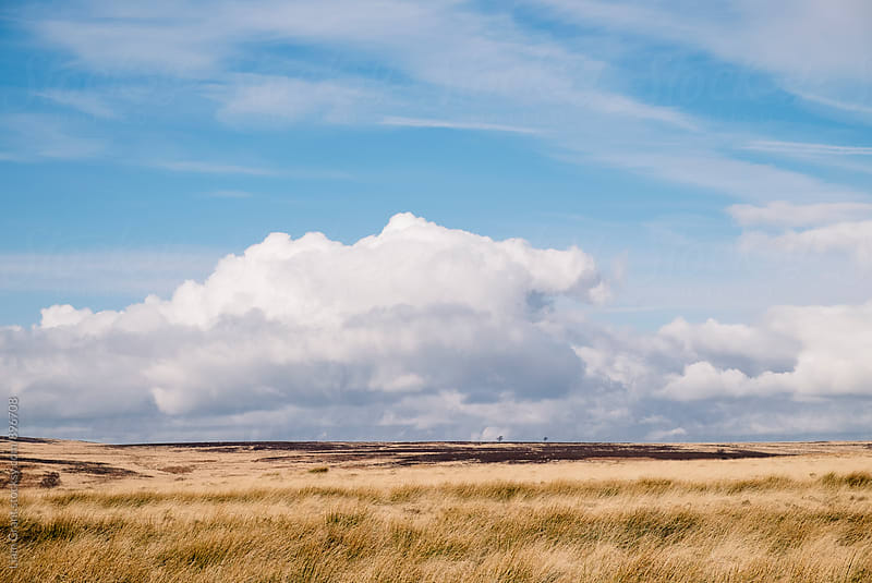 Blue sky and white clouds above sunlit moorland. Derbyshire, UK. by Liam Grant for Stocksy United