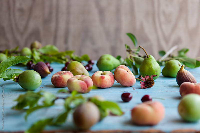 Summer fruits, donut peaches, green pears, cherries, figs and passion fruit by Nadine Greeff for Stocksy United