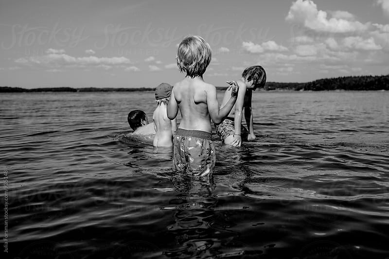 Four children in water in Finland. by Julia Forsman for Stocksy United