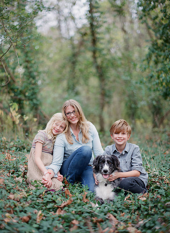 Family photo  standing in ivy woods with their pet dog by Marta Locklear for Stocksy United