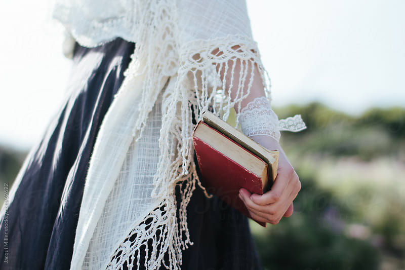 Girl wearing vintage style clothing and carrying old books by Jacqui Miller for Stocksy United