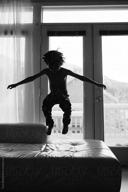 boy with arms out wide as he jumps on the couch by Tara Romasanta for Stocksy United