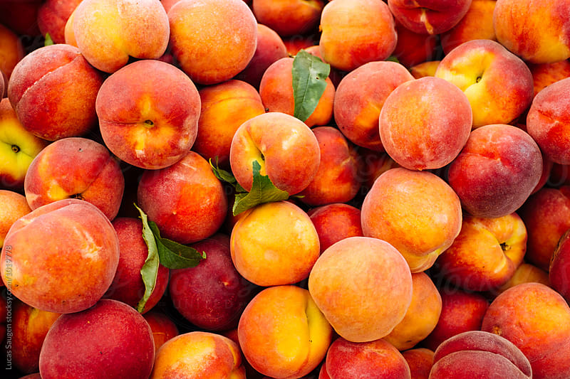 A stack of farm fresh peaches. by Lucas Saugen for Stocksy United