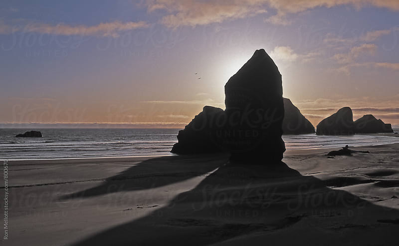 Seastacks silhouetted at late afternoon and low tide at Cape Sebastian, Oregon by Ron Mellott for Stocksy United