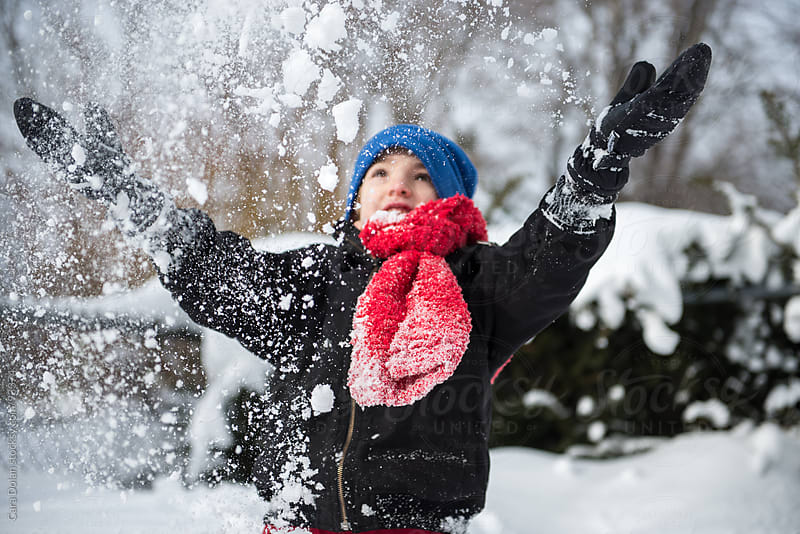 Boy throws freshly fallen snow into the air with joy by Cara Dolan for Stocksy United