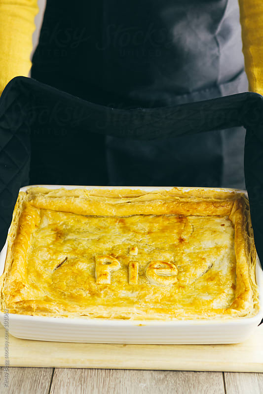 Woman in black apron holding chicken pie with word pie on top by Kirsty Begg for Stocksy United