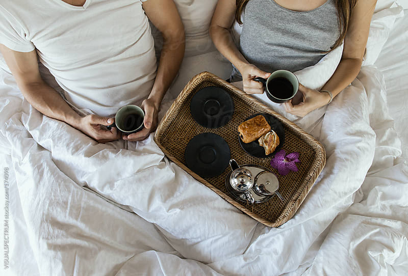 Young Couple Having Coffee in Bed by VISUALSPECTRUM for Stocksy United