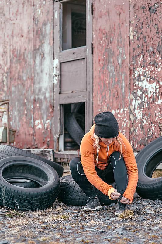 Fitness girl  tying her shoes  by Søren Egeberg Photography for Stocksy United