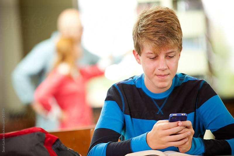 Library: Boy Texting Instead of Doing Homework by Sean Locke for Stocksy United