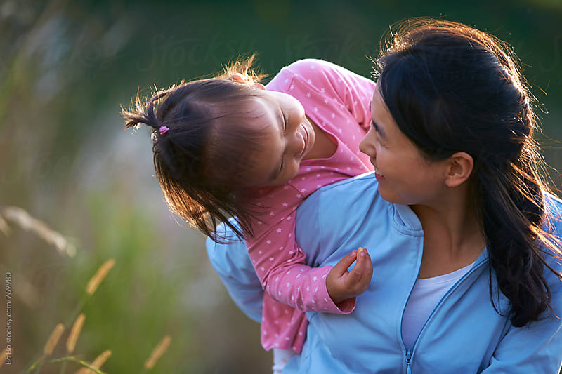 happy little asian girl with her mother outdoor by Bo Bo for Stocksy United