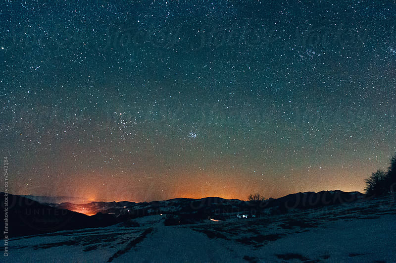 View from mountain on city lights under the starry sky by Dimitrije Tanaskovic for Stocksy United