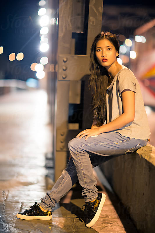 Young Asian Woman Sitting in the Street by Lumina for Stocksy United