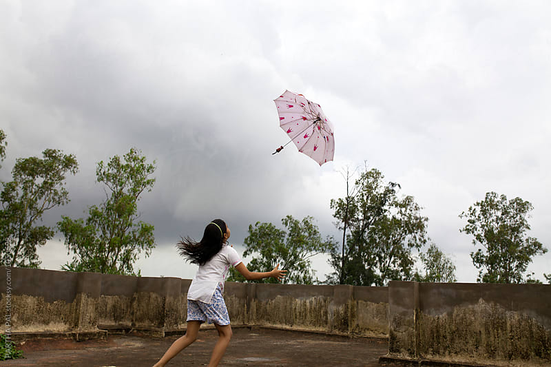 Monsoon season with umbrella in air by PARTHA PAL for Stocksy United