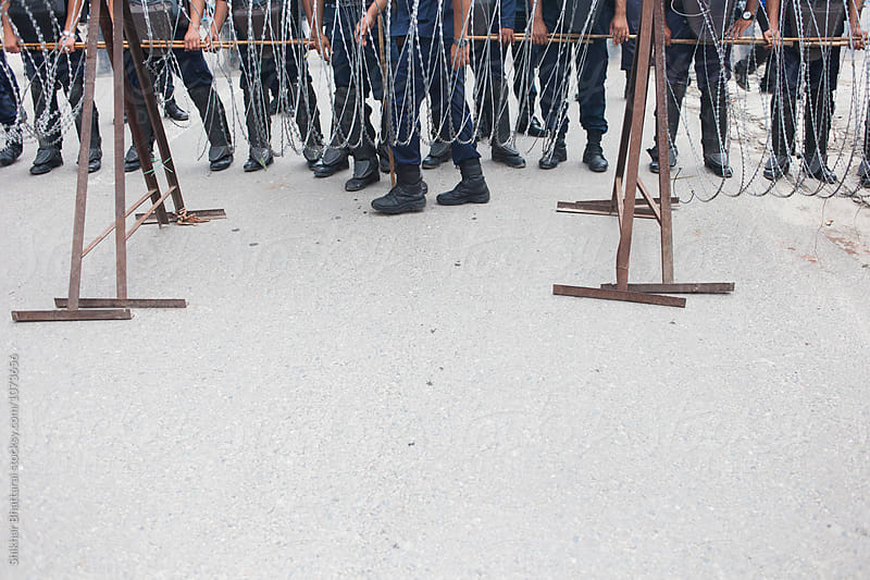 Police barricade during a protest. by Shikhar Bhattarai for Stocksy United