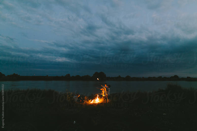 Family around the night fire on river bank by Evgenij Yulkin for Stocksy United