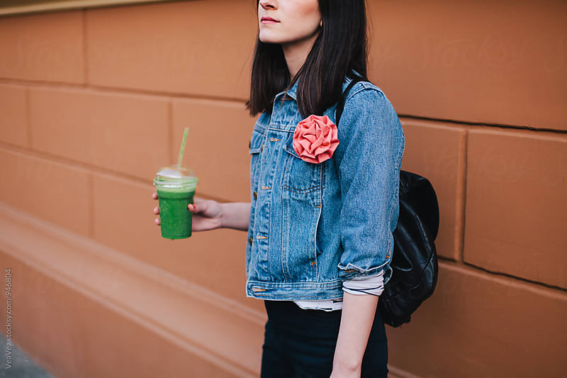Woman holding a green smoothie by Marija Mandic for Stocksy United