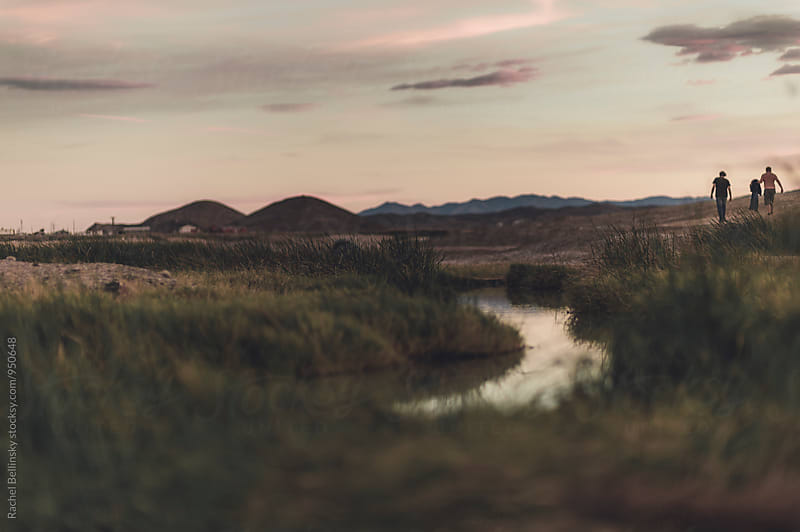 a stream of water fades into a sunset horizon by Rachel Bellinsky for Stocksy United