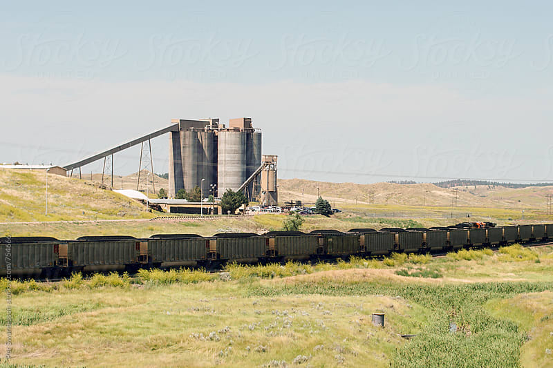 Long coal mine train with coal silos in the background by Per Swantesson for Stocksy United