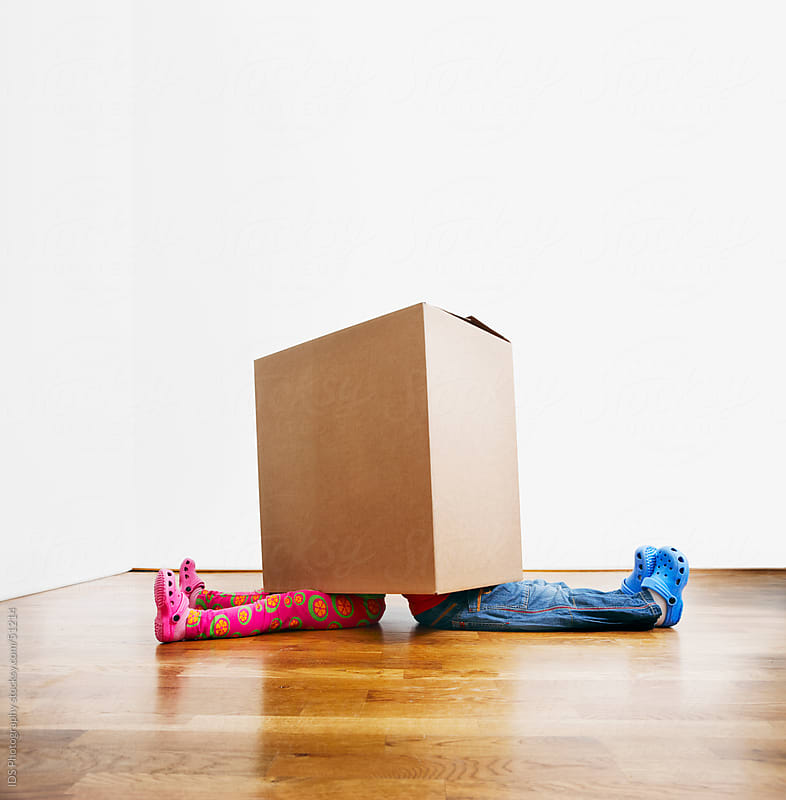 Kids playing with cardboard box like its there new home by IDS Photography for Stocksy United