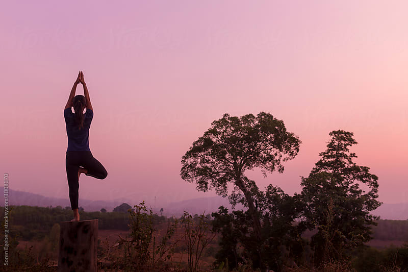 Woman practising yoga at sunrise in the mountains by Soren Egeberg for Stocksy United