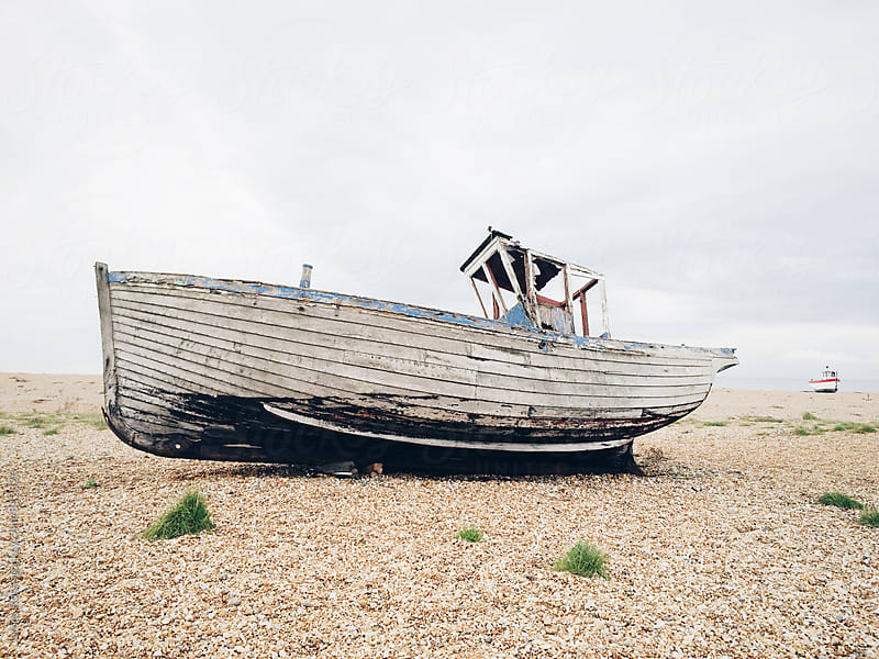 An abandoned boat on a pebble beach by James Ross for Stocksy United