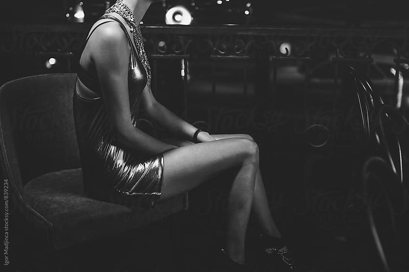 beautiful girl in modern dress with jewelry on a chair in the bar by Igor Madjinca for Stocksy United