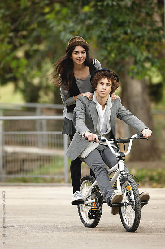 Young couple riding a bike  by Miquel Llonch for Stocksy United