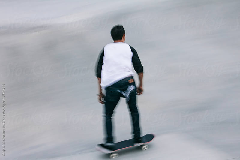 Skater riding skateboard. Speed blurred image by Alejandro Moreno de Carlos for Stocksy United